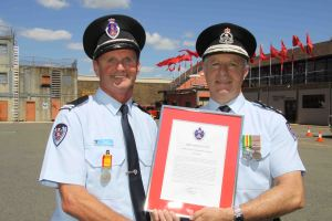 David Weir receiving his commendation from Commissioner Greg Mullins.