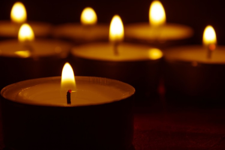 23174019 - burning candles and black background